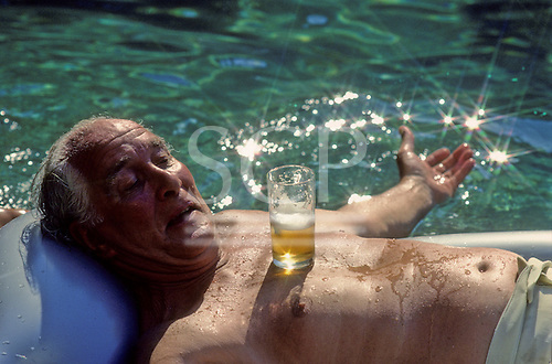 Rio de Janeiro, Brazil. Train robber Ronnie Biggs relaxing with a cool beer in the pool at his home in Santa Tereza in 1990.