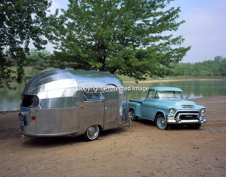 A light blue 1955 GMC pickup parked next to a 1948 Airstream Wee Wind vintage travel trailer.