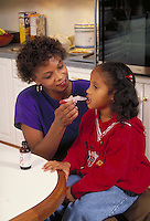 African-american mother gives medicine to daughter