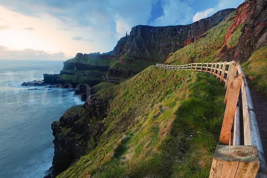 Fenced cliffside trail on Benbane Head near sunset, Giant's Causeway, County Antrim, Northern Ireland, United Kingdon