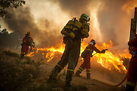 Members of the Brif, reinforcement brigade wildfires, and Emergency Military Unit (UME) work to put out a wildfire in Tabuyo del Monte near Leon on August 20, 2012. Numerous wildfires have broken out across Spain in the sweltering heat in recent weeks, an extra headache for authorities struggling to get the country out of its financial crisis and recession. © Pedro ARMESTRE