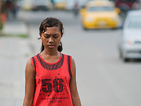 A young woman walks on a busy street in Dili, Timor-Leste (East Timor)