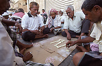 Men playing dominoes on the Prince of Wales Crescent which runs alongside the docks in Aden where British ships refuelled on their voyages between Britian and the east. Aden's location near the entrance to the Red Sea meant that for centuries it dominated east-west trade and was once the British colonial capital of Yemen.