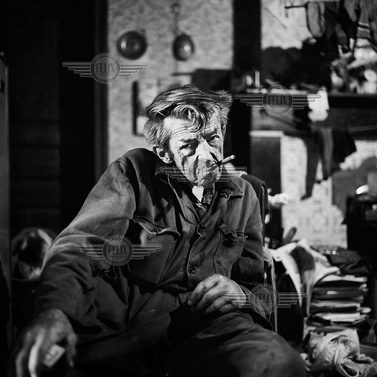 Portrait of Theofiel smoking a cigarette in his house. Theofiel was a bachelor all his life and lived on his own at his farm. He kept cows, pigs and horses. At the end of his life he struggled to keep his farm going due to his frailty.
