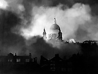 Standing up gloriously out of the flames and smoke of surrounding buildings, St. Paul's Cathedral is pictured during the great fire raid of Sunday December 29th.  London, 1940.
