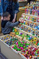 Yangzhou, Jiangsu, China.  Little Boy Examining Small Figurines in a Store on Dong Guan Street.