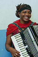 Zanzibar, Tanzania.  Taarab Musicians.  Culture Musical Club.  Woman Playing Accordion.  Note that she is wearing a nose pin.