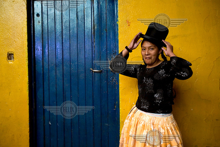 18 year old wrestler Gloria Esperanza (fighting name), Esperanza Gomez (real name) stands outside the changing room at the Multifuncional building where every Sunday wrestling takes place. Esperanza is a Cholita, a wrestler of native Aymara descent. When Cholitas fight they wear traditional costume: colourful dresses and dark bowler hats.