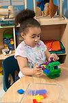 Education preschool 3-4 year olds girl talking to herself while building with bristle blocks in classroom