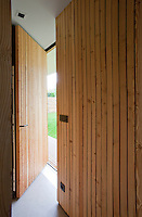 The interior wall and open front door of the property are clad in pine