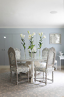 The pale blue dining room with a set of upholstered chairs and built-in cupboards