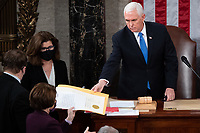US Vice President Mike Pence hands the electoral certificate from the state of Arizona to US Senator Amy Klobuchar, Democrat of Minnesota, as he presides over a joint session of Congress to count the electoral votes for President at the US Capitol in Washington, DC, January 6, 2021.<br /> Credit: Saul Loeb / Pool via CNP/AdMedia