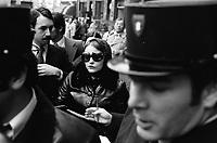 """Picard, Me Cathala, Me Bouscatel, Me Rastoul"""". Place Wilson. 30 novembre 1976. Au 1er plan visage d'un policier ; au 2nd plan plan taille de face d'une femme, lunettes noires, foulard sur la tête, à côté d'elle Christian Portay (un des acusés). Cliché pris le jour d'une reconstitution judiciaire dans le cadre de l'affaire du meurtre de René Trouvé. Observation: Affaire René Trouvé-Birague : le 19 février 1976, le journaliste René Trouvé est assassiné d'une balle dans la tête, par deux inconnus, alors qu'il regagne son domicile au 33 rue Bayard."""