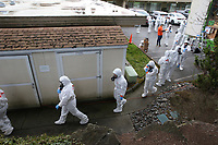 Clean up crews from Servpro gear up and go inside the Life Care Center of Kirkland, the long-term care facility linked to several confirmed coronavirus cases in the state, in Kirkland, Washington, U.S. March 11, 2020.  REUTERS/Karen Ducey