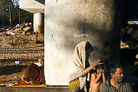 A child picks at her sister's hair for fleas on a piece of waste ground beneath a flyover near Okhla station.