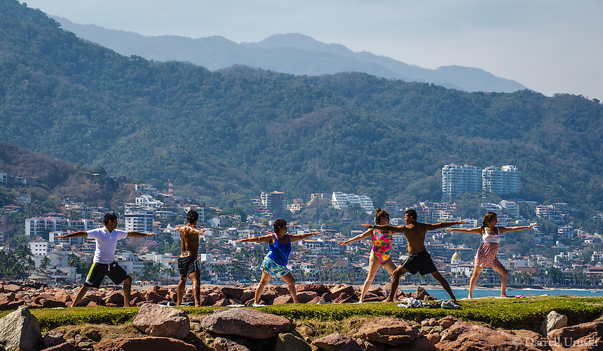 Beach Exercise in Puerto Vallarta. Photograph of a small group of people exercising in front of the picturesque city of Puerto Vallarta in Banderas Bay, Jalisco Mexico.