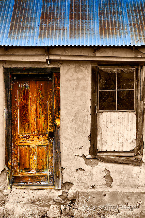 An image of a door, window, and tin roof of an adobe/stone ruin. The door and roof are in color and the window and adobe plastered wall are sepia toned.