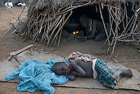 ETHIOPIA, Southern Nations, Lower Omo valley, Kangaten, village Kakuta, Nyangatom tribe, sleeping boy infront of hut / AETHIOPIEN, Omo Tal, Kangaten, Dorf Kakuta, Nyangatom Hirtenvolk, schlafender Junge vor Huette