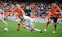 Aberdeen's Niall McGinn goes down as he tries to get away from United's Willo Flood and Keith Watson but referee Iain Brines waves play on  ...