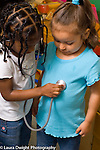 Preschool 3 year ods pretend play two girls playing together one using toy stethoscope on the other