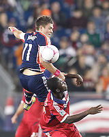 New England Revolution midfielder Kelyn Rowe (11) and Chicago Fire midfielder Patrick Nyarko (14) battle for head ball. In a Major League Soccer (MLS) match, the New England Revolution (blue) defeated Chicago Fire (red), 1-0, at Gillette Stadium on October 20, 2012.