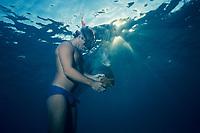 JoJo, a wild sociable bottlenose dolphin, Tursiops truncatus, or ambassador dolphin, examines a starfish or sea star held by friend Dean Bernal, Providenciales Turks and Caicos Islands, Caribbean Sea, (W. Atlantic Ocean)