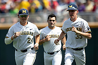 Michigan Wolverines players Casey Buckley (24), Joe Pace (32)and Walker Cleveland (35) warm up during Game 1 of the NCAA College World Series against the Texas Tech Red Raiders on June 15, 2019 at TD Ameritrade Park in Omaha, Nebraska. Michigan defeated Texas Tech 5-3. (Andrew Woolley/Four Seam Images)