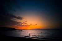 A woman enjoys the last of the day's sunset at a camping beach in Kailua-Kona, Big Island.