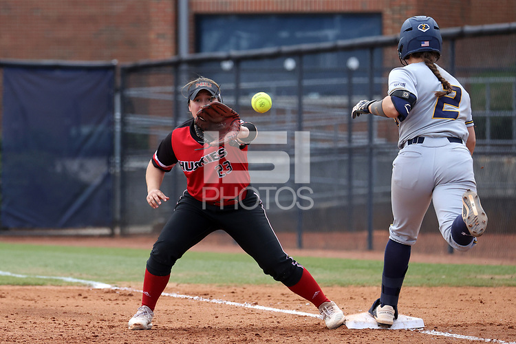 GREENSBORO, NC - MARCH 11: Delaney Cumbie #2 of UNC Greensboro is safe at first base, beating the throw to Anne Allen #23 of Northern Illinois University during a game between Northern Illinois and UNC Greensboro at UNCG Softball Stadium on March 11, 2020 in Greensboro, North Carolina.