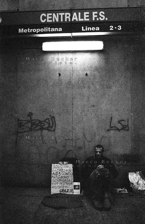 milano, stazione centrale. ragazzo senzatetto e malato di aids fa elemosina nel passaggio per la metropolitana --- milan, central station. young homeless and aids sufferer begging in the passing to the subway