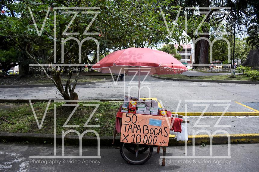 ARMENIA - COLOMBIA, 21-06-2021: Una venta ambulante de tapabocas es vista en medio de la pandemia de coronavirus en Bogotá, Colombia. Según el último informe oficial del Ministerio de Salud y Protección Social, Colombia registra 99.934 víctimas del COVID-19. Con más de 500 fallecidos en las últimas 24 horas el país espera llegar a las 100.000 víctimas hoy. / Facemask street vendor is seen amid the coronavirus pandemic in Bogotá, Colombia. According to the latest official report from the Ministry of Health and Social Protection, Colombia registers 99,934 victims of COVID-19. With more than 500 deaths in the last 24 hours, the country expects to reach 100,000 victims today. Photo: VizzorImage / Santiago Castro / Cont