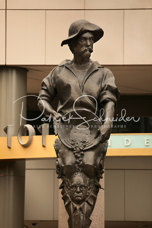 The city of Charlotte has four statues on the corners of the main square of the city, the corners of Trade Street and Tryon Street. This figure, of a gold miner spilling money on the head of a banker, represents Commerce. The three other statues represent Future, Industry and Transportation. American sculptor Raymond Kaskey created the four public art statues. Some people say the face of the banker is modeled after Federal Reserve Chairman Alan Greenspan.