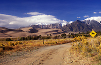 USA, Colorado, Great Sand Dunes National Park, dirt road  and sand dunes with Sangre de Cristo Mountains with horseback riding sign