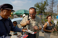 Man handing out souvenirs to tourists at the Yungang Grottoes, Shanxi, China.