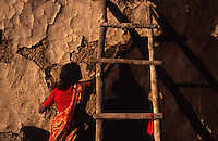 INDIA Madhya Pradesh, woman repairs clay wall in Adivasi village /  INDIEN, Frau verputzt Lehmwand in einem Adivasi Dorf