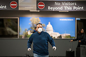 A man wears a protective mask as he and other passengers arrive from Dubai after a 14-hour flight on Emirates flight 231, at the international terminal at Dulles International Airport in Dulles, Va., Monday, March16, 2020. Some people are taking the precaution of wearing face masks as they arrive to be greeted by family and or friends. Credit: Rod Lamkey / CNP