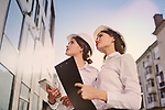 M1MYNX Two young pretty business women industrial engineers in construction helmets with a tablet in hands on a glass building background