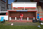 Shildon 0 Warrington Rylands 0 (4-5 pens), 17/04/2021. Dean Street, FA Vase Fourth Round. A home team's substitute sits in the dugout before Shildon take on Warrington Rylands in an FA Vase Fourth Round tie at Dean Street. Formed in 1890, the home club are members of the Northern League Division One with their rivals playing in the North West Counties League Premier Division. The away team won the match 5-4 on penalties after a 0-0 draw over 90 minutes, in a fixture played without spectators permitted due to ongoing Covid-19 restrictions. Photo by Colin McPherson.