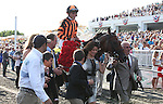 LITTLE MIKE and jockey Ramon A. Dominguez are lead into the winner's circle by owner Pricilla Vaccarezza after winning the Arlington Million at Arlington Park 8-18-12