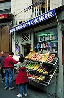 Tourists outside Latin Quarter produce shop on rue de la Montagne Ste. Genevieve. Flats of fruits and vegetables on sidewalk rack and drugstore items in window. Man reads Paris map. Paris, France.