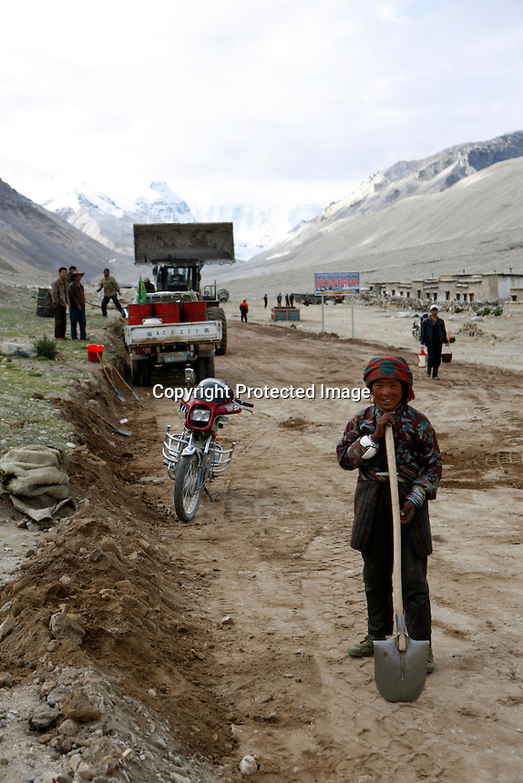 """China started building a controversial 67-mile """"paved highway fenced with undulating guardrails"""" to Mount Qomolangma, known in the west as Mount Everest, to help facilitate next year's Olympic Games torch relay./// A young woman works with a shovel building the road to Everest Base Camp.<br /> Tibet, China<br /> July, 2007"""