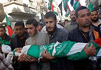 """Mourners bury the bodies of two Palestinian children from Abu Maateq family at the end of their funeral in Beit Lahia in the northern Gaza Strip on April 28, 2008. Four children, aged one to five, their mother and a militant were killed in Israeli operations in Gaza today as Palestinian factions headed to Egypt for talks on a possible truce. The four siblings -- aged one, three, four and five -- were killed when a tank shell hit their home in the town of Beit Hanun, and their mother died later of her wounds, doctors at the Kamal Radwan hospital said.""""photo by Fady Adwan"""""""