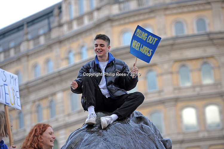 """Protestors on top of one of the lions at the base of Nelsons Column in Trafalgar Square in London during the """"Put it to the People"""" rally which made it's way through central London today. Demonstrators from across the country gathered to call for a second referendum on Brexit and to march through the UK capital finishing with speeches in Parliament Square opposite the Houses of Parliament in Westminster."""