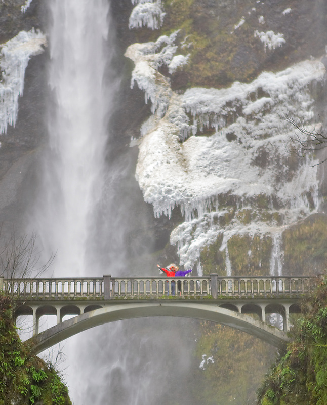 People on bridge at Multnomah Falls with winter ice. Oregon