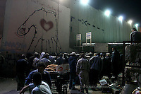 """Palestinian workers lined up next to the Separating Wall in Bethlehem as they wait to cross the """"Gilo Terminal"""" in order to work in Jerusalem. According to UNRWA thousands workers cross the Gilo Terminal from all Southern West Bank. With the economic crises in the West Bank, workers try to get permits and take the long journey to work in Israel. Next week Pope Benedict XVI will visit Bethlehem. Photo by Quique Kierszenbaum"""