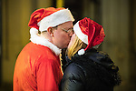 """© Joel Goodman - 07973 332324 . 17/12/2016 . Manchester , UK . A man and woman dressed as Santa Claus share a kiss , on Deansgate . Revellers out in Manchester City Centre overnight during """" Mad Friday """" , named for being one of the busiest nights of the year for the emergency services in the UK . Photo credit : Joel Goodman"""