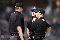 Umpires Eric Gillam (left), Alex Tosi (center) and Brian Peterson get together to discuss a call during the International League game between the Durham Bulls and the Charlotte Knights at BB&T BallPark on May 15, 2017 in Charlotte, North Carolina. The Knights defeated the Bulls 6-4.  (Brian Westerholt/Four Seam Images)