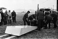 21 avril 1972. Au 1er plan des hommes sont en train de mettre le cercueil de Didier Daurat dans la caveau ; au 2nd plan vue de face de la famille et des amis autour du caveau, parapluies ; en arrière-plan avions sur la piste de Montaudran, brouillard, pluie. Cliché pris lors de la cérémonie organisée dans le cadre du transfert du corps de Didier Daurat dans un caveau en bordure de la piste de Montaudran.