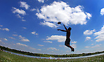 A cloud-dotted summer sky sprawls over Dustin Medearis of Pleasant Hill, leaping for a Frisbee while playing catch at Raccoon River Park on June 29.