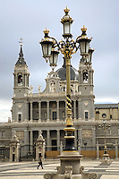 Spain. Province of Madrid. Madrid. Catedral Santa María la Real de La Almudena ( Catholic cathedral ) and the Plaza de la Armas which is a vast square. Both are located south of the Palacio Real de Madrid (Royal Palace of Madrid), also called Palacio de Oriente (Palace of Orient). The palace is located on Bailén street, in the western part of downtown Madrid. Japanese tourists. Golden street lamps. © 2007  Didier Ruef